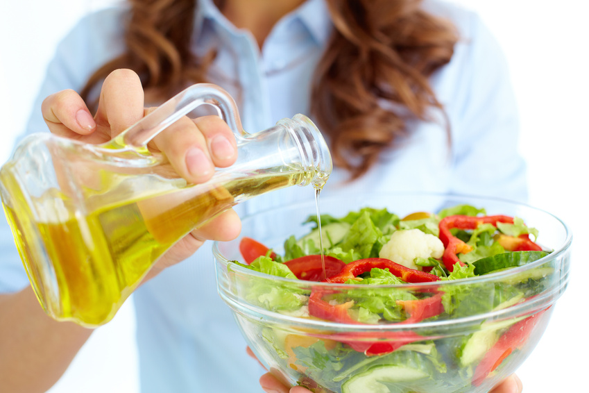 Close-up of female pouring oil into vegetable salad in glass bowl